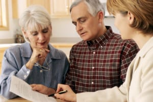 Mature couple talking to eldercare resource consultant.