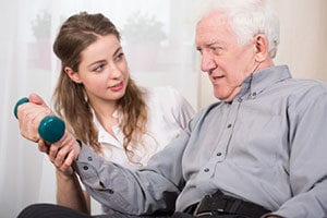 In home care professional assisting elderly man with physical therapy