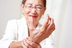 senior holdiing arm showing early signs of a stroke