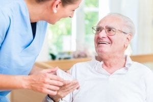 senior man receiving prescription medication from his senior in-home care provider
