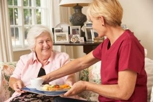 senior receiving a plate of food from an employee of a Rockville, MD in-home care agency