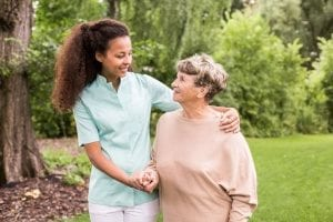 in-home care agency assisting an elderly woman with walking, which is one of the adls