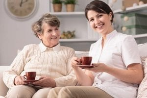 senior woman and an in-home care giver drinking tea and enjoying spending quality time together in the house