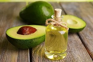 avocados laying next to a bottle of avocado oil which are supposedly healthy brain foods for the elderly since they are rich in multiple vitamins