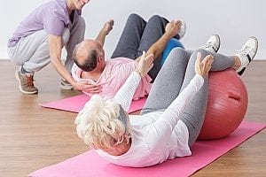 man and woman demonstrating some of the best exercises for senior health which include different types of squats while laying down and using a squat ball