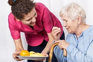 an in-home care agent serving her senior patient foods while discussing the 6 activities of daily living with her