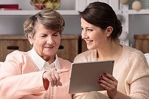 employee of an in-home care agency working with her senior patient to compile a list of household chores that need to be done by the caregiver