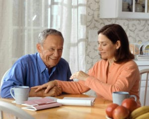Elderly man with in-home caretaker sitting at table