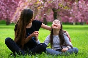 special needs in-home care provider playing outside with a young girl with special needs