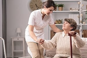 an elder woman receiving help from an in home care agent to help significantly reduce her fall risk