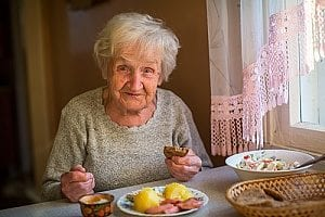 an elderly woman performing one of the ADL activities by feeding herself at home