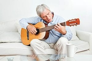 elderly man playing guitar because playing musical instruments is one of the best of elderly mental exercises