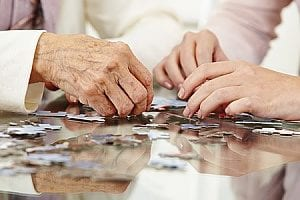 elderly person making a puzzle with family which is popular among elderly mental exercises
