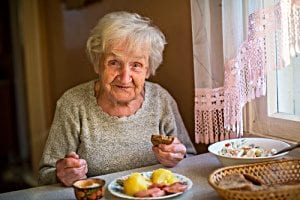 elderly woman eating at home; feeding oneself is a ADL activity