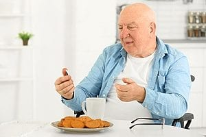 a senior receiving recovery care by being provided with breakfast