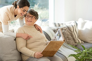 caregiver gently hugging elderly woman with photo album smiling