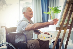senior man using in home mobility equipment for seniors to paint a picture