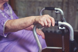 woman using a walker to have one of the best in home mobility equipment for seniors