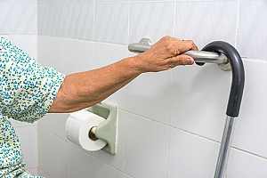 a senior woman who is holding onto a grab bar while bathing