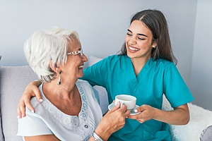 a Washington, DC in home caregiver assisting a love one with drinking tea